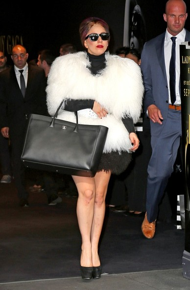 Lady Gaga dresses in a large white fur coat and black dress as she leaves Sephora Champs-Elysees after promoting her perfume, Fame.
