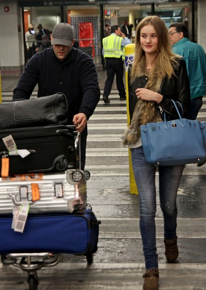 Jason Statham and Rosie Huntington-Whitely arrive at Miami International Airport and cart their own luggage outside.