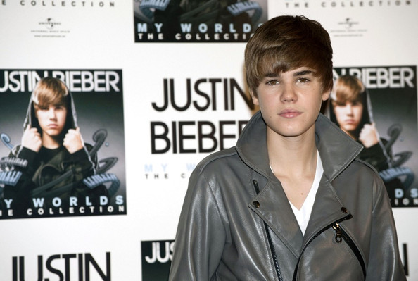 Justin Bieber receives a gold disc during a press conference.