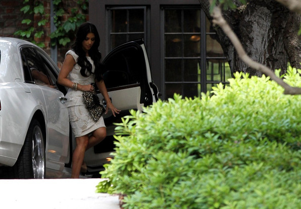 Kim Kardashian Kim Kardashian emerges from a car toting a leopard print clutch as she arrives at a friends house.
