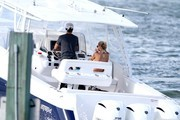 Anna Kournikova keeps a protective hand on her stomach while wearing a bikini as she and fiance, Enrique Iglesias go for a boat ride with their dogs in the waters near their home.