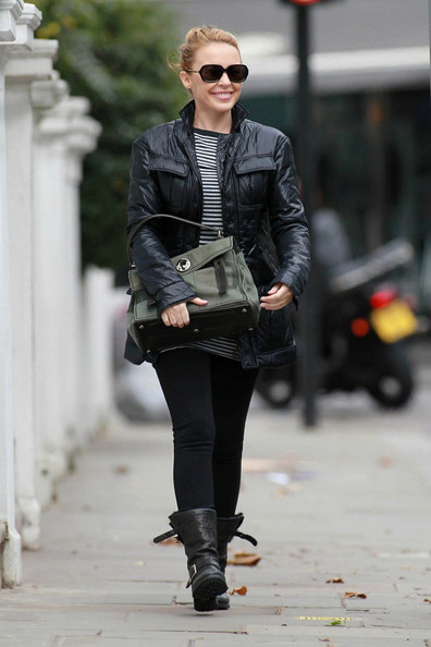 Kylie Minogue looks as if she is ready to go on a motorbike ride as she leaves her house in a fitted black leather jacket and black boots.