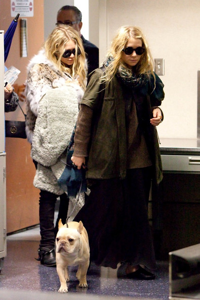 Mary-Kate Olsen Mary Kate and Ashley Olsen, with her dog, arrive at LAX (Los Angeles International Airport) on a rainy day.