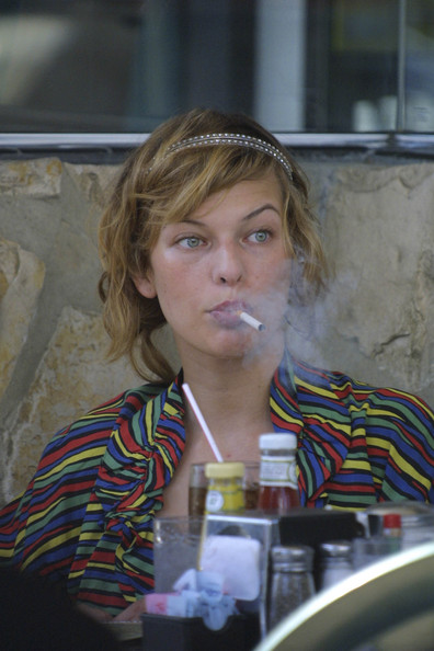 Milla Jovovich smoking a cigarette (or weed)