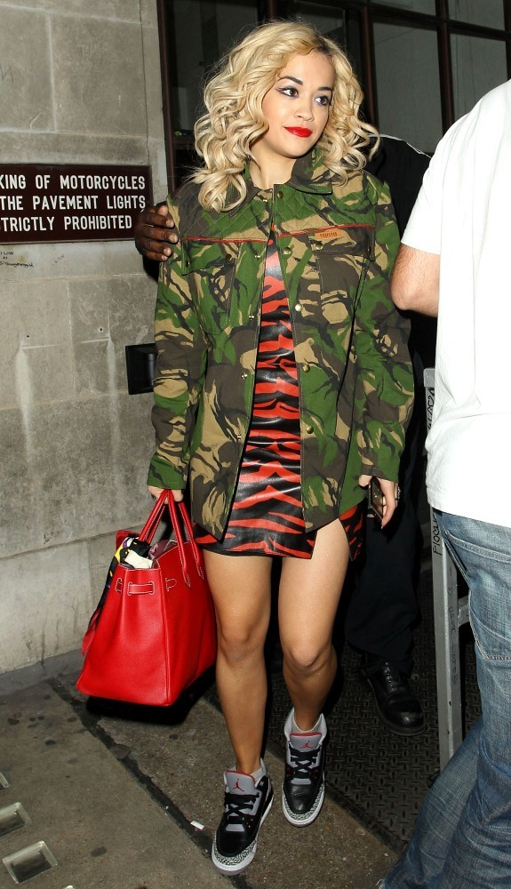 Rita Ora leaves BBC Radio One studios in a zebra print vinyl dress and camouflage jacket.[KGC-49/182].