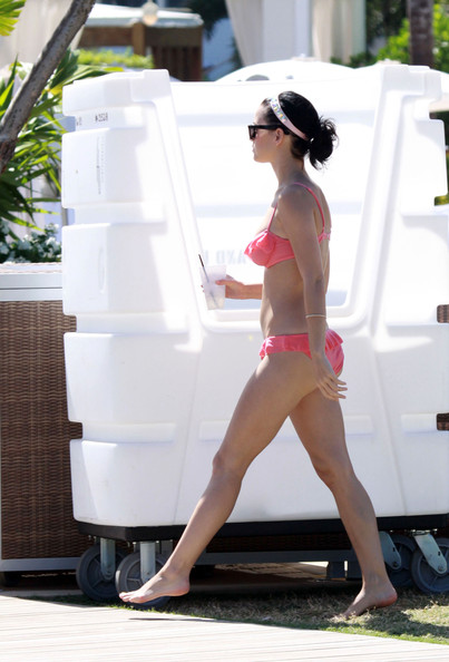 Singer Katy Perry hangs around a stage set in a girly pink bikini following a beach concert.