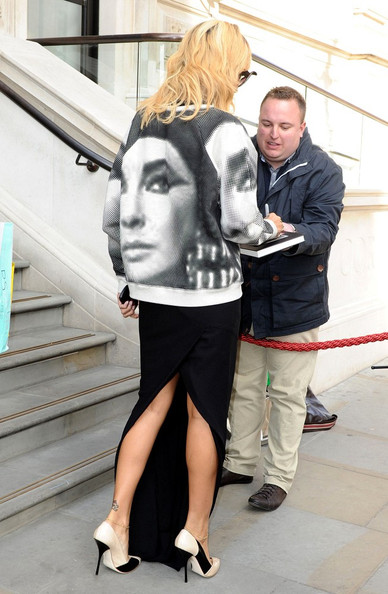 Rihanna wears an Elizabeth Taylor print sweatshirt from Topshop over a long black skirt as she leaves her hotel.