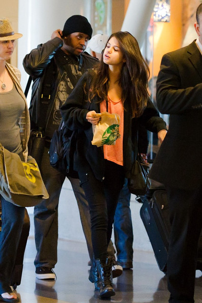 Selena Gomez Having just landed a few hours before Justin Bieber is back at Los Angeles International Airport (LAX). Bieber does his best to hide as he stops at Starbucks with his girlfriend Selena Gomez and their entourage .