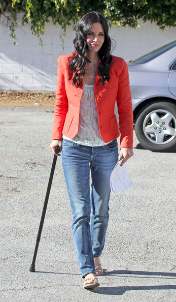 Actress Courteney Cox with the aid of a walking stick limps to the set of her TV Show Cougar Town. Cox told photographers that she had tore her meniscus and had to have knee surgery.