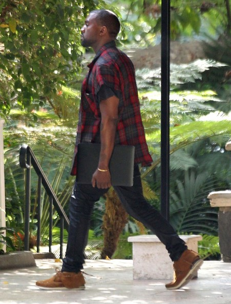 After returning from his trip to San Francisco where he proposed to girlfriend Kim Kardashian, Kanye West is seen leaving a business meeting before heading over to the Hollywood Center Studios in Beverly Hills, California on October 24, 2013.