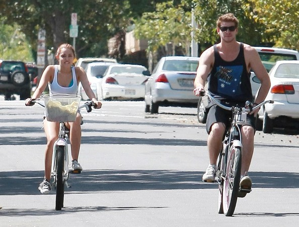 Miley Cyrus and her boyfriend Liam Hemsworth riding their bikes to a 7-11 convenience store to get a Slurpee where they see her dad Billy Ray before returning home in Toluca, CA.