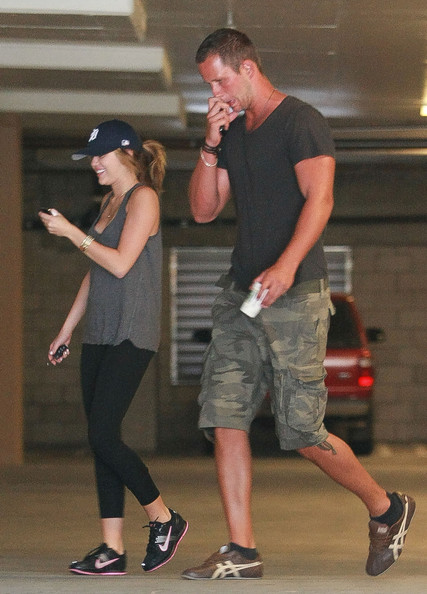 Miley Cyrus Actress Miley Cyrus heads to the gym with her personal trainer in Los Angeles. She's seen wearing her Detroit Tigers hat and playing with her iPhone 4.