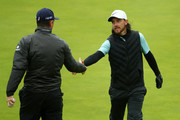 Tommy Fleetwood of England (R) shakes hands Justin Rose of England during a practice round prior to the 148th Open Championship held on the Dunluce Links at Royal Portrush Golf Club on July 17, 2019 in Portrush, United Kingdom.