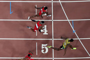 Usain Bolt of Jamaica (R) wins gold ahead of (bottom to top) Andre De Grasse of Canada, Asafa Powell of Jamaica, Justin Gatlin of the United States, Tyson Gay of the United States, Mike Rodgers of the United States and Trayvon Bromell of the United States as they cross the finish line in the Men's 100 metres final during day two of the 15th IAAF World Athletics Championships Beijing 2015 at Beijing National Stadium on August 23, 2015 in Beijing, China.