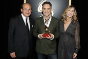 Jorge Drexler (C) poses with the Best Singer-Songwriter Album award with Latin Recording Academy Chairs Eduardo Hutt (L) and Eva Cebrian (R) backstage at the Premiere Ceremony during the 19th Annual Latin GRAMMY Awards at MGM Grand Hotel & Casino on November 15, 2018 in Las Vegas, Nevada.