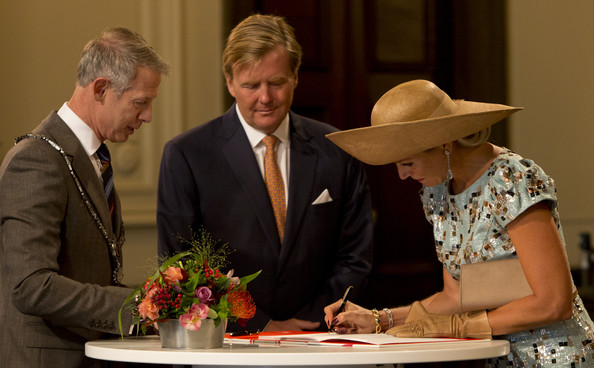 King Willem-Alexander of The Netherlands watches as Queen Maxima of The Netherlands signs the guest book in the city hall as they attend celebrations marking the 200th anniversary of the kingdom of The Netherlands on August 30, 2014 in Maastricht, The Netherlands.