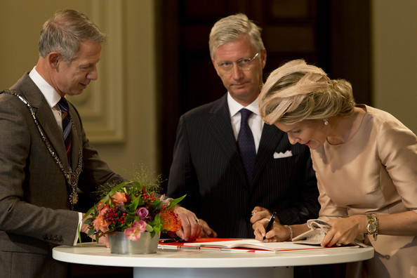 King Philippe of Belgium watches Queen Mathilde of Belgium sign the guest book in the city hall as they attend celebrations marking the 200th anniversary of the kingdom of The Netherlands on August 30, 2014 in Maastricht, The Netherlands.