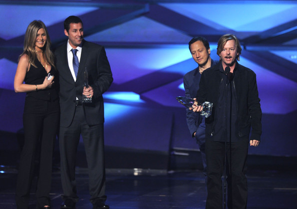 Actor David Spade (R) accepts the Favorite Comedy Movie award with presenter actress Jennifer Aniston (L) actor Adam Sandler (2nd L) and actor Rob Schneider (2nd R) onstage during the 2011 People's Choice Awards at Nokia Theatre L.A. Live on January 5, 2011 in Los Angeles, California.