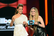 Presenters Alyssa Milano and Avril Lavigne speak onstage during the 2013 Billboard Music Awards at the MGM Grand Garden Arena on May 19, 2013 in Las Vegas, Nevada.