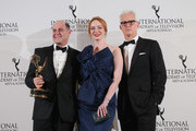 Emmy Founders Award recipient, Creator, Executive Producer, Writer of Mad Men Matthew Weiner (L) poses with his award and presenters (C-R) Christina Hendricks and John Slattery at the 2014  International  Academy Of Television Arts & Sciences Emmy Awards at New York Hilton on November 24, 2014 in New York City.