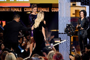 Carrie Underwood (C) walks onstage to accept the Favorite Female Artist - Country award from Sara Gilbert during the 2018 American Music Awards at Microsoft Theater on October 9, 2018 in Los Angeles, California.