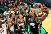 Chris Staples (R, holding mobile device) poses for a selfie photo with fellow participants such as Big Tigger, YFN Lucci, Big Boy, Casanova, Erica Ash, Brittney Elena, Kamaiyah, Lecrae, Doug Christie, Jahi Winston, and Christian Keyes at the Celebrity Basketball Game Sponsored By Sprite during the 2018 BET Experience at Los Angeles Convention Center on June 23, 2018 in Los Angeles, California.