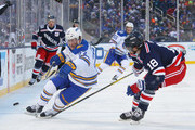 Johan Larsson #22 of the Buffalo Sabres controls the puck against Marc Staal #18 of the New York Rangers during the 2018 Bridgestone NHL Winter Classic at Citi Field on January 1, 2018 in New York, New York.