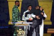 (L-R) Actors Winston Duke, Chadwick Boseman, and Michael B. Jordan, winners of the Best Movie award (Presented by Toyota) for 'Black Panther,' and host Tiffany Haddish speak onstage during the 2018 MTV Movie And TV Awards at Barker Hangar on June 16, 2018 in Santa Monica, California.