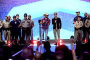 Jason Aldean (center L) and Bobby Bones (center R) speak onstage with first responders during the 2018 iHeartRadio Music Festival at T-Mobile Arena on September 21, 2018 in Las Vegas, Nevada.