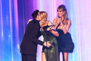 Taylor Swift (C) accepts the Favorite Album - Pop/Rock award for 'Lover' from Dan Levy (L) and Heidi Klum (R) onstage during the 2019 American Music Awards at Microsoft Theater on November 24, 2019 in Los Angeles, California.