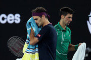 Novak Djokovic of Serbia walks past Roger Federer of Switzerland during change of ends in their Men's Singles Semifinal match on day eleven of the 2020 Australian Open at Melbourne Park on January 30, 2020 in Melbourne, Australia.