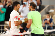 Novak Djokovic of Serbia (L) shakes hands with Rafael Nadal of Spain after winning their Men's Singles Semi Final match against on day Thirteen of the 2021 French Open at Roland Garros on June 11, 2021 in Paris, France.