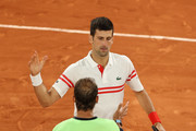 Novak Djokovic of Serbia (Top) shakes hands with Rafael Nadal of Spain after winning their Men's Singles Semi Final match against on day Thirteen of the 2021 French Open at Roland Garros on June 11, 2021 in Paris, France.