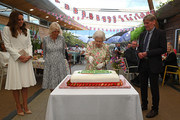 Watched over by Catherine, Duchess of Cambridge (L), Camilla, Duchess of Cornwall (2nd L) and Board director of Eden Project, Peter Stewart (R), Queen Elizabeth II (C) eventually cuts a cake with a knife, to celebrate of The Big Lunch initiative at The Eden Project during the G7 Summit on June 11, 2021 in St Austell, Cornwall, England. UK Prime Minister, Boris Johnson, hosts leaders from the USA, Japan, Germany, France, Italy and Canada at the G7 Summit. This year the UK has invited India, South Africa, and South Korea to attend the Leaders' Summit as guest countries as well as the EU.