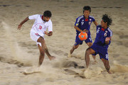 Moslem Mesigar of Iran shoots at goal under pressure from Takasuke Goto and Masahito Toma (R) of Japan in the Beach Soccer match between Iran and Japan at Al-Musannah Sports City during day five of the 2nd Asian Beach Games Muscat 2010 on December 12, 2010 in Muscat, Oman.