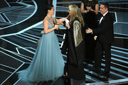 Producer Darla K. Anderson (C) and co-director Lee Unkrich (R) accept Best Animated Feature Film for 'Coco' from actor Kelly Marie Tran (L) onstage during the 90th Annual Academy Awards at the Dolby Theatre at Hollywood & Highland Center on March 4, 2018 in Hollywood, California.