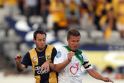Joshua Rose of the Mariners is challenged by Ufuk Talay of the Fury during the round 19 A-League match between the Central Coast Mariners and the North Queensland Fury at Bluetongue Stadium on December 22, 2010 in Gosford, Australia.