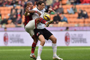 Nigel De Jong (L) of AC Cesena competes with Milan Djuric of AC Milan during the Serie A match between AC Milan and AC Cesena at Stadio Giuseppe Meazza on February 22, 2015 in Milan, Italy.