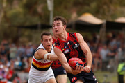 Tim Smith of the Demons is tackled by Tom Doedee of the Crows during the 2018 AFL round 10 match between the Melbourne Demons and the Adelaide Crows at TIO Traeger Park on May 27, 2018 in Alice Springs, Australia.