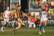 Brad Sewell of the Hawks kicks under pressure from Daniel Harris of the Suns during the round 13 AFL match between the Hawthorn Hawks and the Gold Coast Suns at Aurora Stadium on June 18, 2011 in Launceston, Australia.