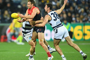 Dom Tyson of the Demons handballs whilst being tackled by Jack Henry of the Cats  during the round 18 AFL match between the Geelong Cats and the Melbourne Demons at GMHBA Stadium on July 21, 2018 in Geelong, Australia.