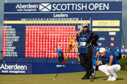 Justin Rose of England and his caddie Mark Fulcher line up a putt on the 18th green during the final round of the Aberdeen Asset Management Scottish Open at Royal Aberdeen on July 13, 2014 in Aberdeen, Scotland.