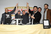 """Founder & CEO of Goldbelly, Joe Ariel (L) and Adam Richman (3rdR) raise the winners arms for the best sandwich """"The Bomb"""" by Sal, Kris and Charlie's, The Sandwich King of Astoria along with Jeremy Jacobowitz (2ndR) and Frank Luciano (R) at America's Greatest Sandwich Showdown during New York City Wine & Food Festival at Highline Stages on October 13, 2019 in New York City."""