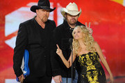 Co-hosts Trace Adkins (L) and Kristin Chenoweth (R) present recording artist Toby Keith (C) with the Artist of the Decade award at the American Country Awards at the MGM Grand Garden Arena December 5, 2011 in Las Vegas, Nevada.