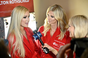 (L) Paris Hilton and Nicky Hilton Rothschild prepare backstage at The American Heart Association's Go Red For Women Red Dress Collection 2020 at Hammerstein Ballroom on February 05, 2020 in New York City.