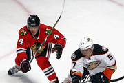 David Perron #57 of the Anaheim Ducks and Niklas Hjalmarsson #4 of the Chicago Blackhawks move to the puck at the United Center on February 13, 2016 in Chicago, Illinois. The Ducks defeated the Blackhawks 3-2 in overtime.
