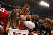 Intern linebacker coach Jen Welter of the Arizona Cardinals signs autographs for a young girl following the team training camp at University of Phoenix Stadium on August 2, 2015 in Glendale, Arizona.