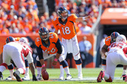 Quarterback Peyton Manning #18 of the Denver Broncos runs the offense as center Manny Ramirez #66 waits to snap the ball int he first quarter of a game against the Arizona Cardinals at Sports Authority Field at Mile High on October 5, 2014 in Denver, Colorado.