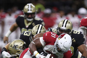 Tim Scott #31 of the Arizona Cardinals is tackled by Manti Te'o #51 of the New Orleans Saints  at Mercedes-Benz Superdome on August 17, 2018 in New Orleans, Louisiana.