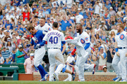 Anthony Rizzo #44 of the Chicago Cubs is mobbed by Albert Almora Jr. #5 (L), Willson Contreras #40 (C) and Jason Heyward #22 (R) after hitting a walk-off home run in a win over the Arizona Diamondbacks at Wrigley Field on July 26, 2018 in Chicago, Illinois. The Chicago Cubs won 7-6.